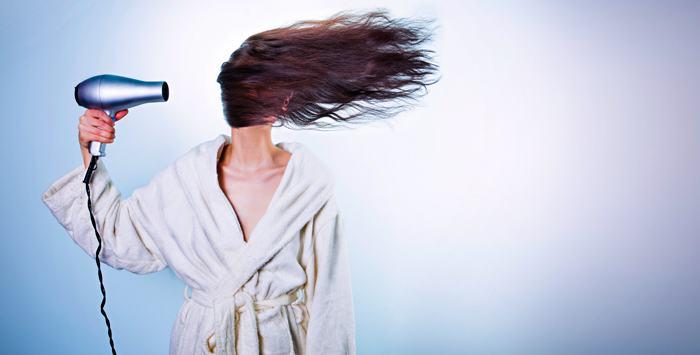 femeie ce își usucă părul